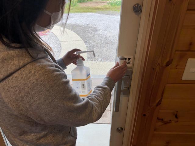 玄関ドアの消毒。